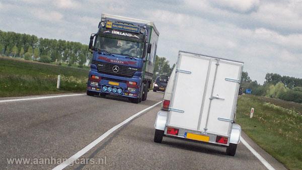 Auto met aanhangwagen en tegemoetkomende vrachtwagen op rijksweg