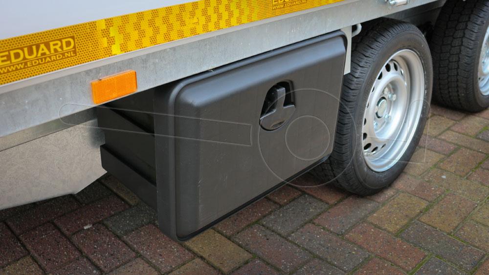 Materiaalkist gemonteerd aan de onderzijde van de laadbak op een plateau aanhangwagen