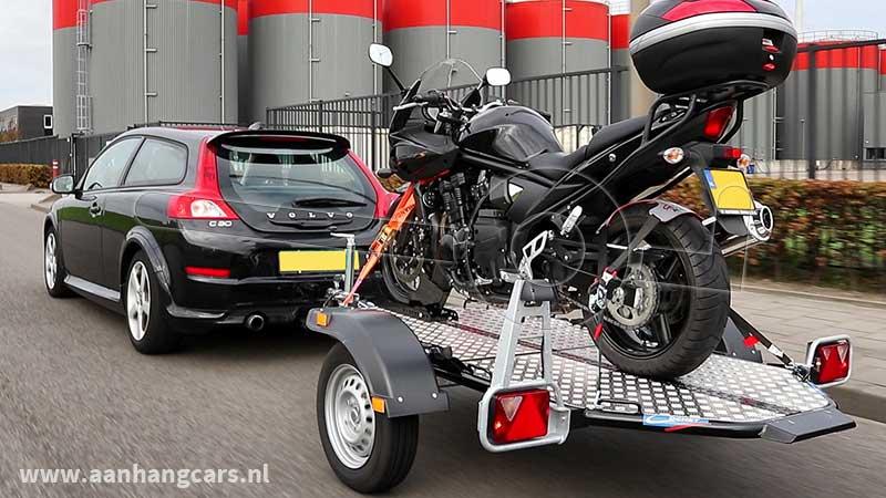 Rijdende auto met aangekoppelde Cochet Uno verlaagbare motortrailer waarop één motor staat