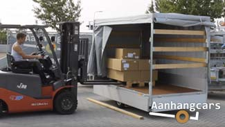 Vorkheftruck plaatst een pallet met dozen in de laadbak van een Eduard plateauwagen die is voorzien van een huif