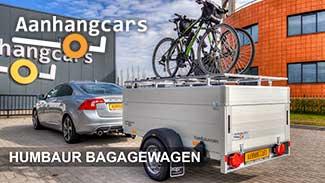 Humbaur aluminium bagagewagen met fietsen op het deksel aangekoppeld achter een personenauto