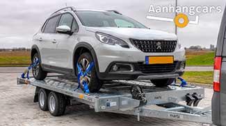 Een kantelbare Martz tandemas autotransporter met rijbanen waar reen personenauto op staat