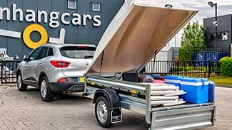 Zilverkleurige auto met daarachter een, met vakantiespullen beladen, Martz bagagewagen met geopend deksel en geopende achterklep