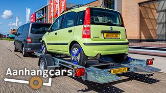 Rijdende bestelbus met daarachter een Martz enkelas kantelbare autotransporter waar een kleine groende stadsauto staat