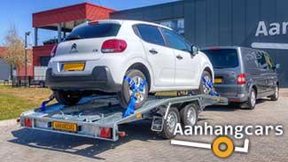 Martz tandemas autotransporter met rijbanen die aan voor- en achterzijde schuin aflopen waarop een kleine auto staat.
