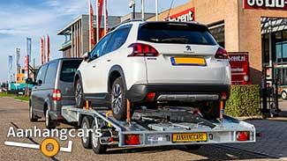 Martz tandemas autotransporter met schuin aflopende achterzijde beladen met een witte personenauto achter een bestelbus