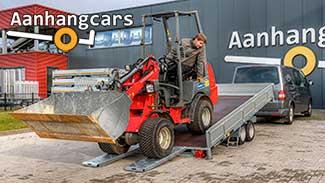 Martz kantelbare multitransporter met oprijplaten waar een kleine rode shovel opgereden wordt