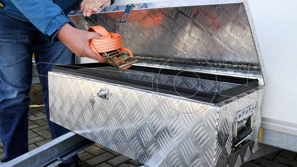 Persoon pakt een spanband uit de materiaalkist op de dissel van een gesloten aanhangwagen