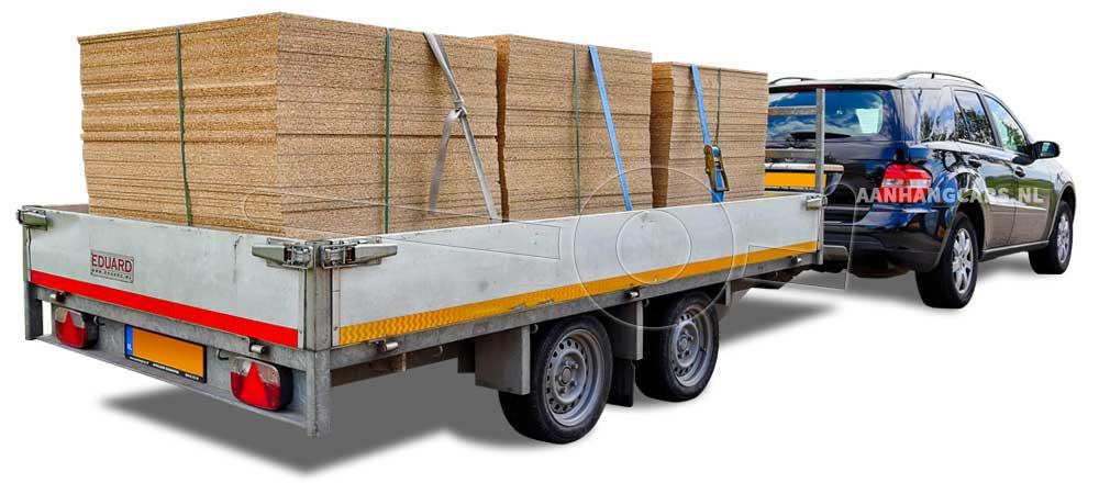Een plateauwagen beladen met stapels houten platen achter een auto