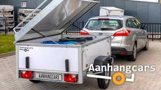 Een beladen Power Trailer bagagewagen met geopend deksel achter een grijze stationwagen