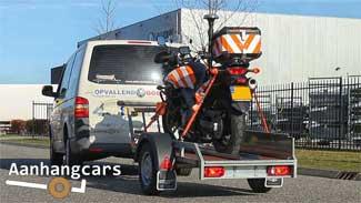 Twins Trailer motortrailer waar een motor van een verkeersregelaar is geladen aangekoppeld aan een witte bestelbus