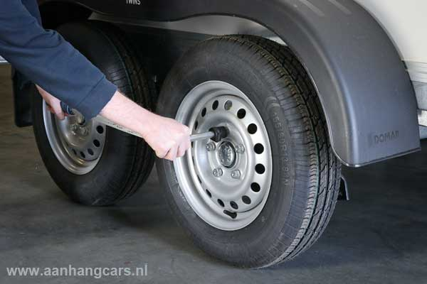 Monteur trekt wielbouten van aanhangwagen aan